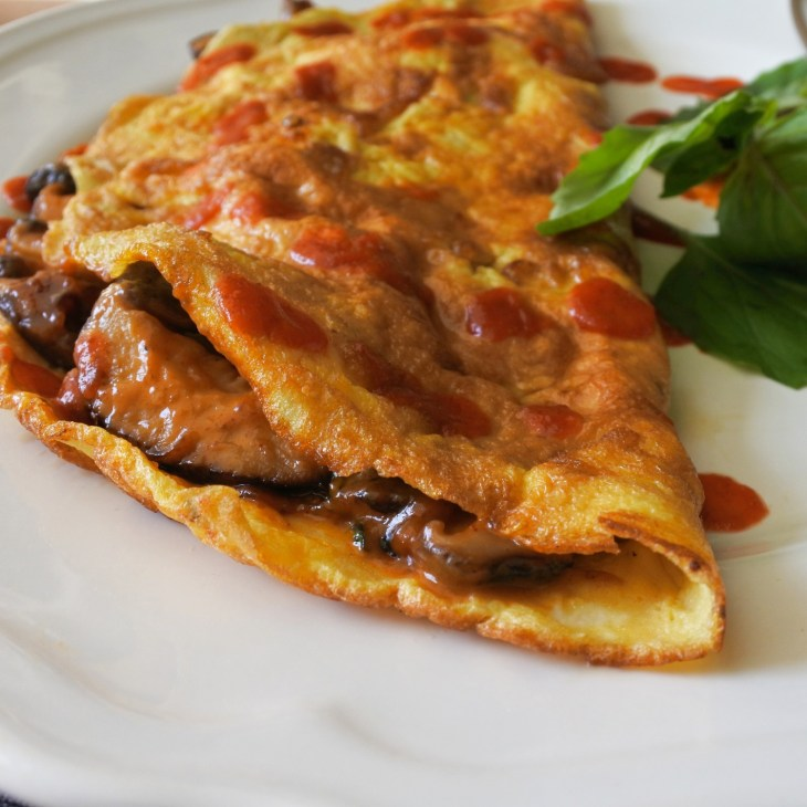 omelette filled with Thai chile mushrooms garnished with Thai basil and sriracha