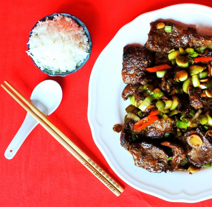 Chinese style liver and onions on a plate with rice, chopsticks and spoon