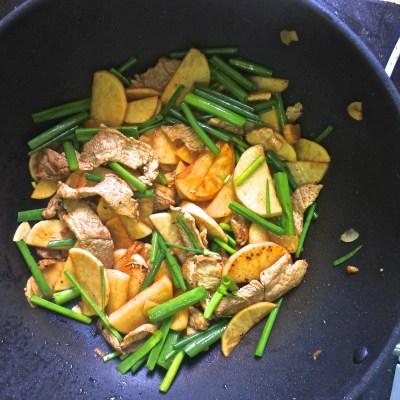 pork, daikon and scallion stalks frying in wok