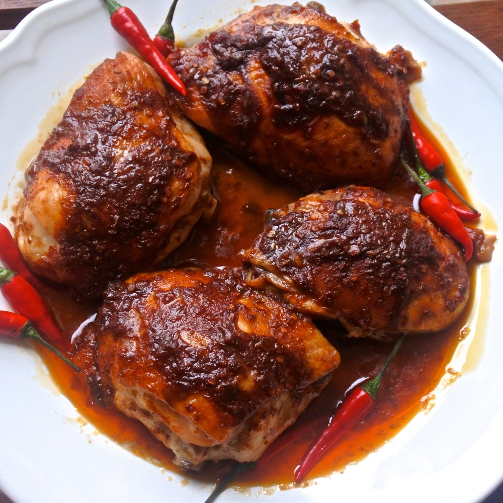 Piri Piri Chicken thighs on a plate with red chiles