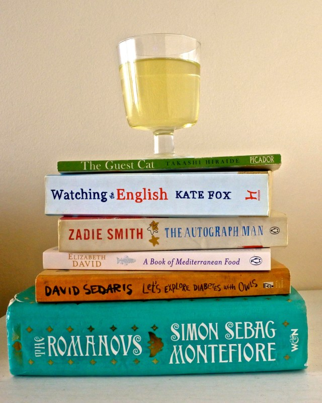 glass of white wine atop a stack of books