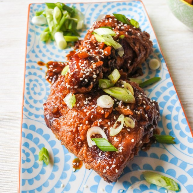 Garlic and ginger fried chicken garnished with sesame seeds and scallions