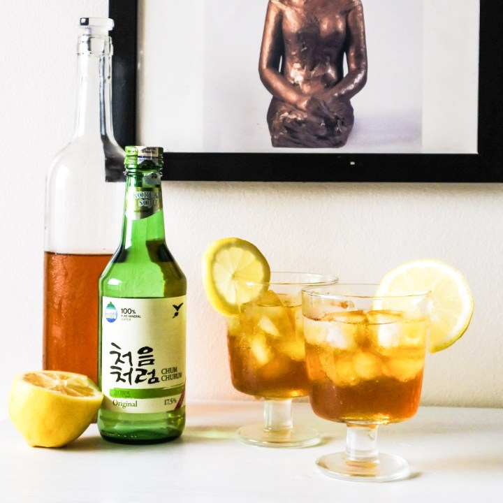 a bottle of green tea syrup, Korean soju bottle and lemon with cocktails