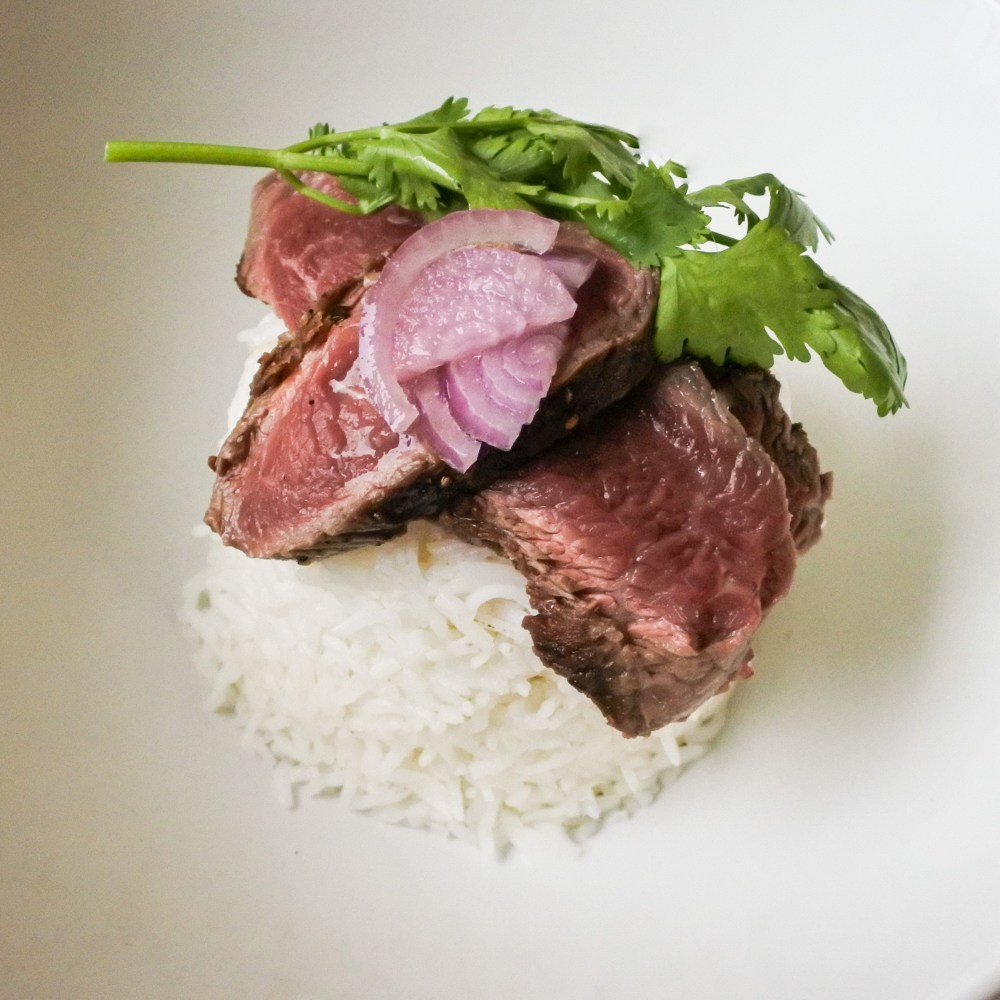 sliced seared beef topside atop Basmati rice with fresh cilantro