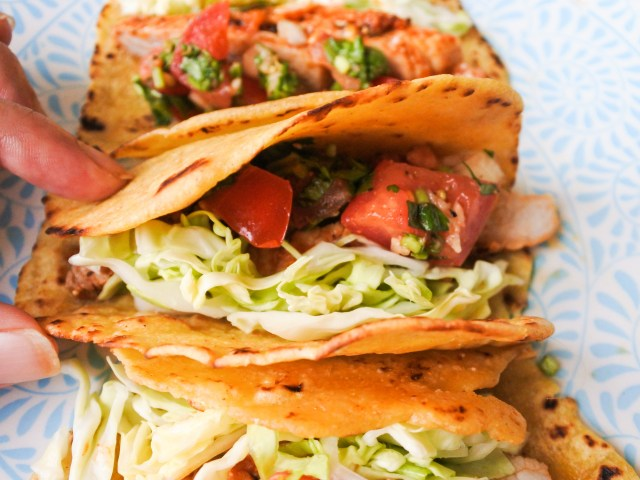 slow cooked pork, salsa and cabbage in folded tortillas on plate
