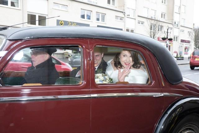 bride and groom in vintage car