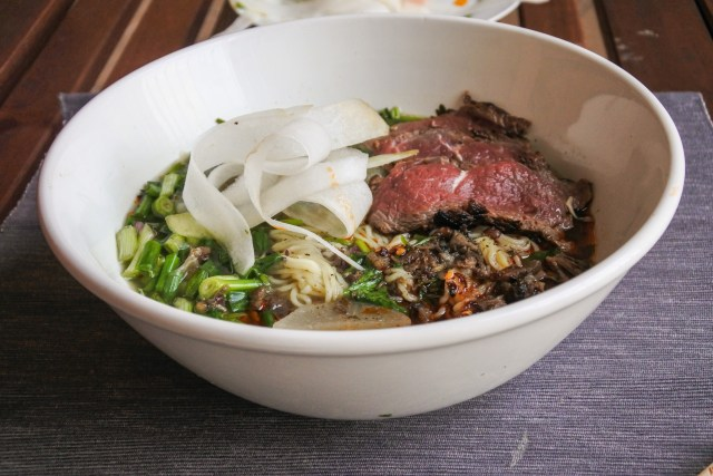noodles in a Chinese beef brother with white radish, seared beef, chopped cilantro and scallion and chili oil