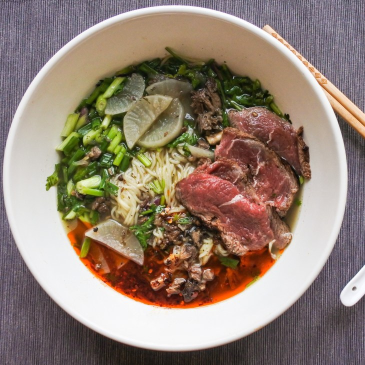 nirou lamian in an oversized bowl with chopsticks and spoon