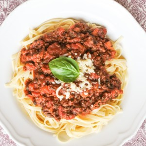 A plate of linguine covered in meat sauce and garnished with Basil and cheese