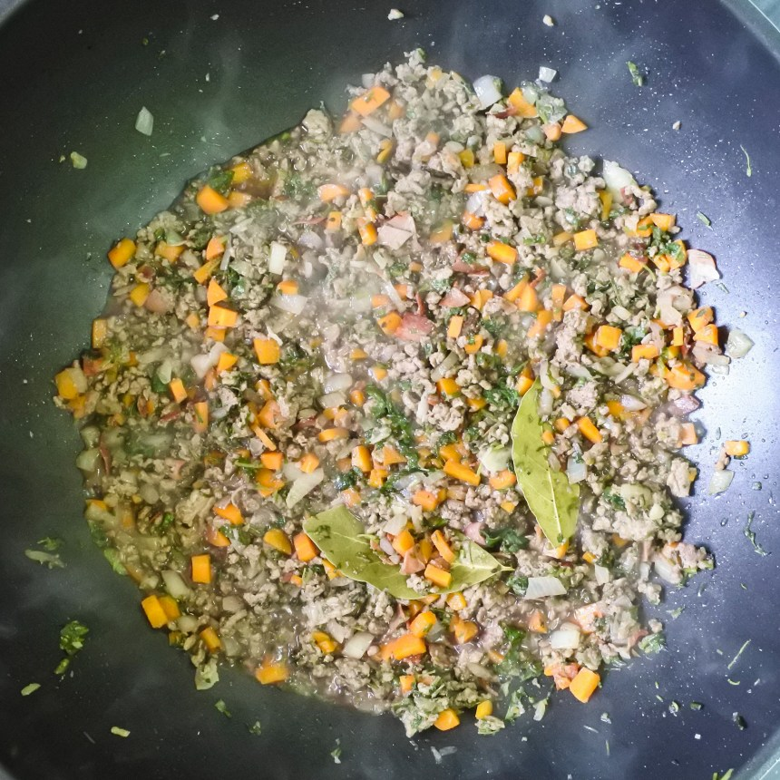 minced beef and diced vegetables cooking in red wine