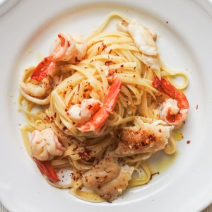 A plate of linguine tossed with fresh seafood and garnished with red pepper flakes