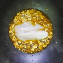 fillet of fish cooking white wine, garlic, chili and olive oil