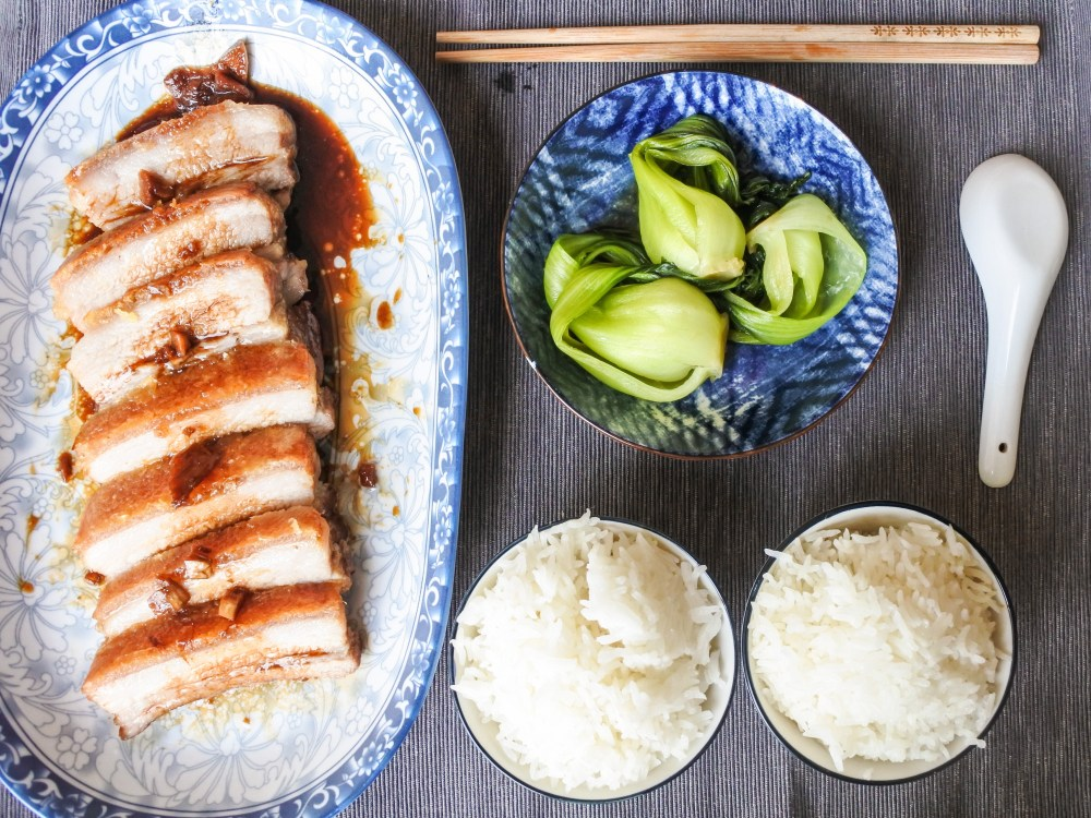 crispy pork belly garnished with a soy glaze served alongside steamed rice and bak choy