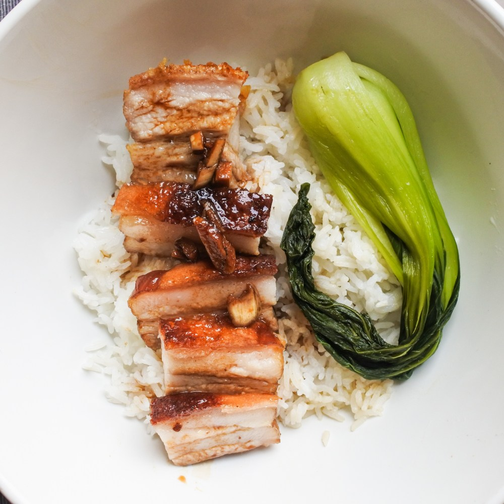 crispy pork belly over steamed rice with bak choy and a soy glaze