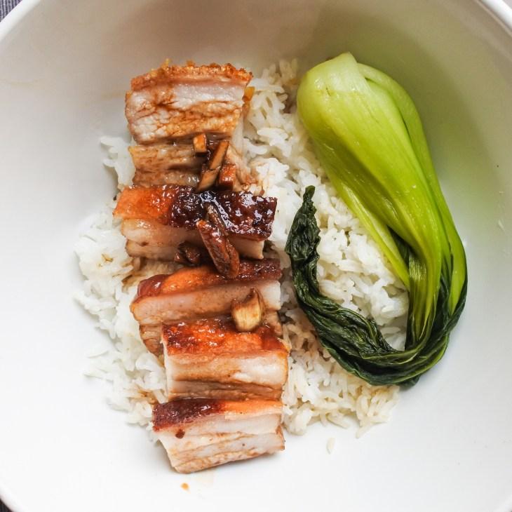 crispy pork belly over steamed rice with bak choy and a soy glaze