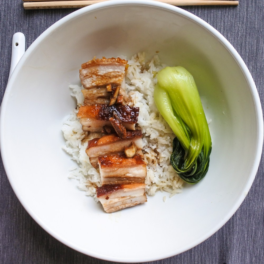 crispy pork belly over steamed rice with bak choy
