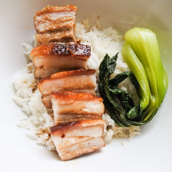 crispy pork belly over steamed rice with bak choy