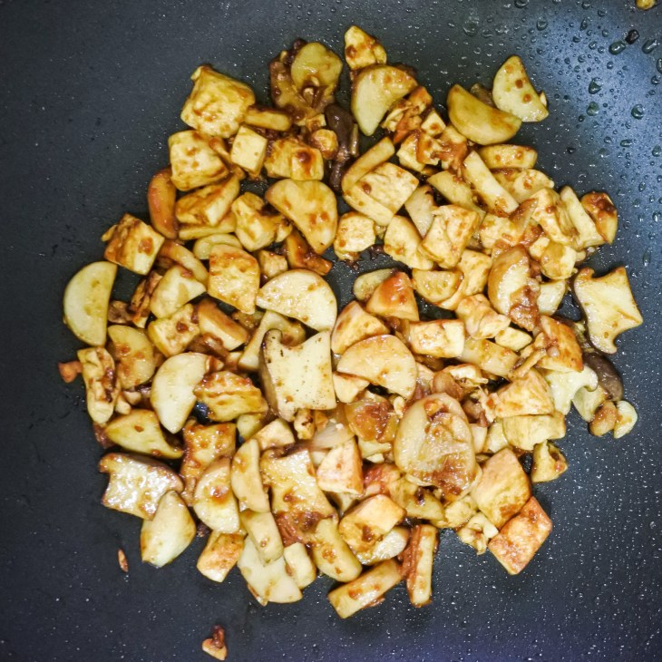 tofu and mushrooms stir fry frying in soybean sauce in a wok