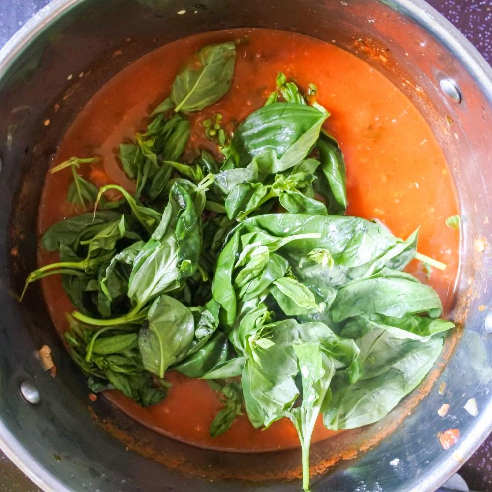 Fresh basil leaves atop tomato soup