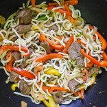 beef, vegetables and noodles frying in wok