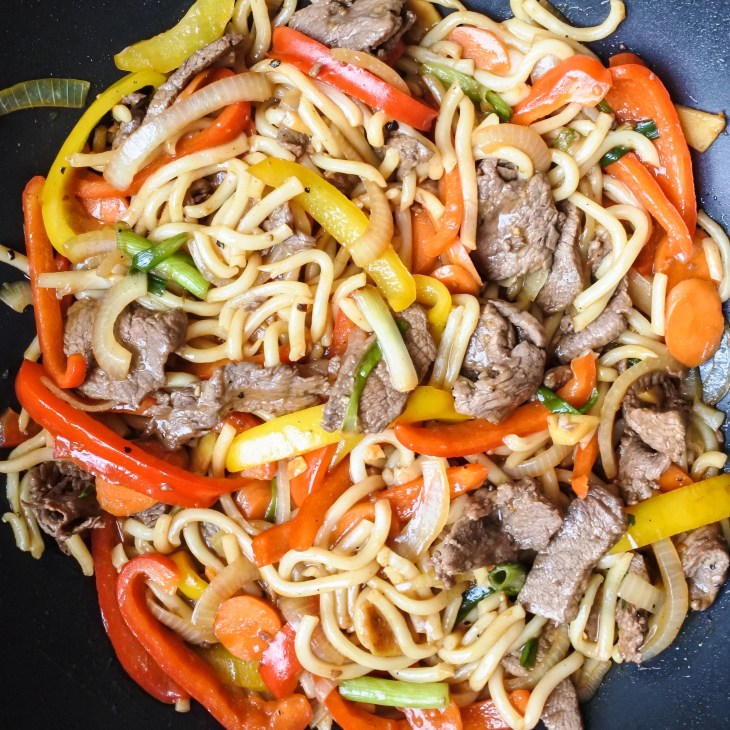 wok fried beef noodles cooking in sauce