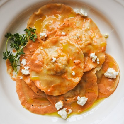 Gently toss ravioli with sauce and garnish with a sprinkling of goats' cheese.
