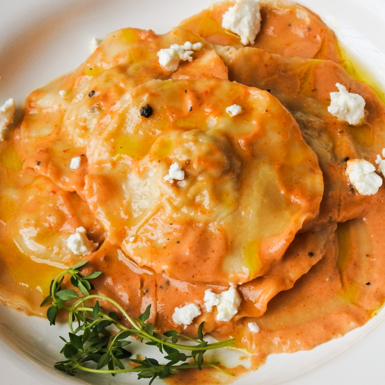Chicken Ravioli with Sun-Dried Tomato Cream Sauce garnished with a sprig of thyme and goat cheese