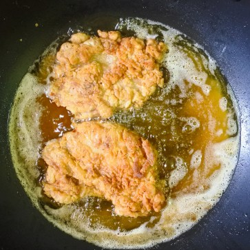 Depending on the size, you'll want the chicken chop to cook in the oil anywhere from 15-20 minutes in order to get the skin crispy and meat fully cooked.  Keep oil hot but not so hot that the outside burns before the center is cooked.  Keep the oil at a steady medium high heat with a fairly moderate bubble.  Nothing too hot or with a furious sizzle.