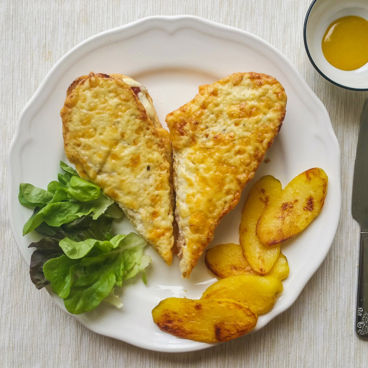 Croque Monsieur, potato frites and lettuce on a plate with a side of Dijon