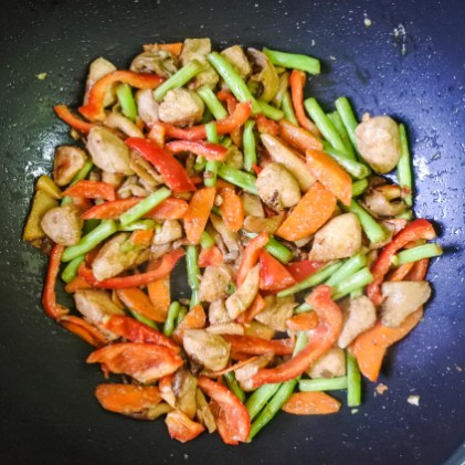 red bell pepper, vegetables and chicken cooking in a wok