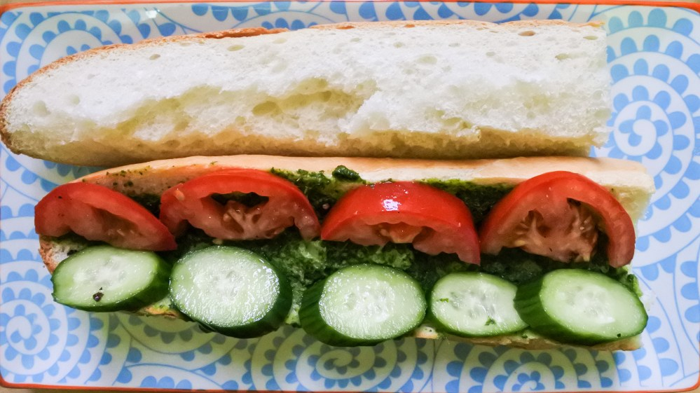 slice cucumber, tomato and pesto on baguette