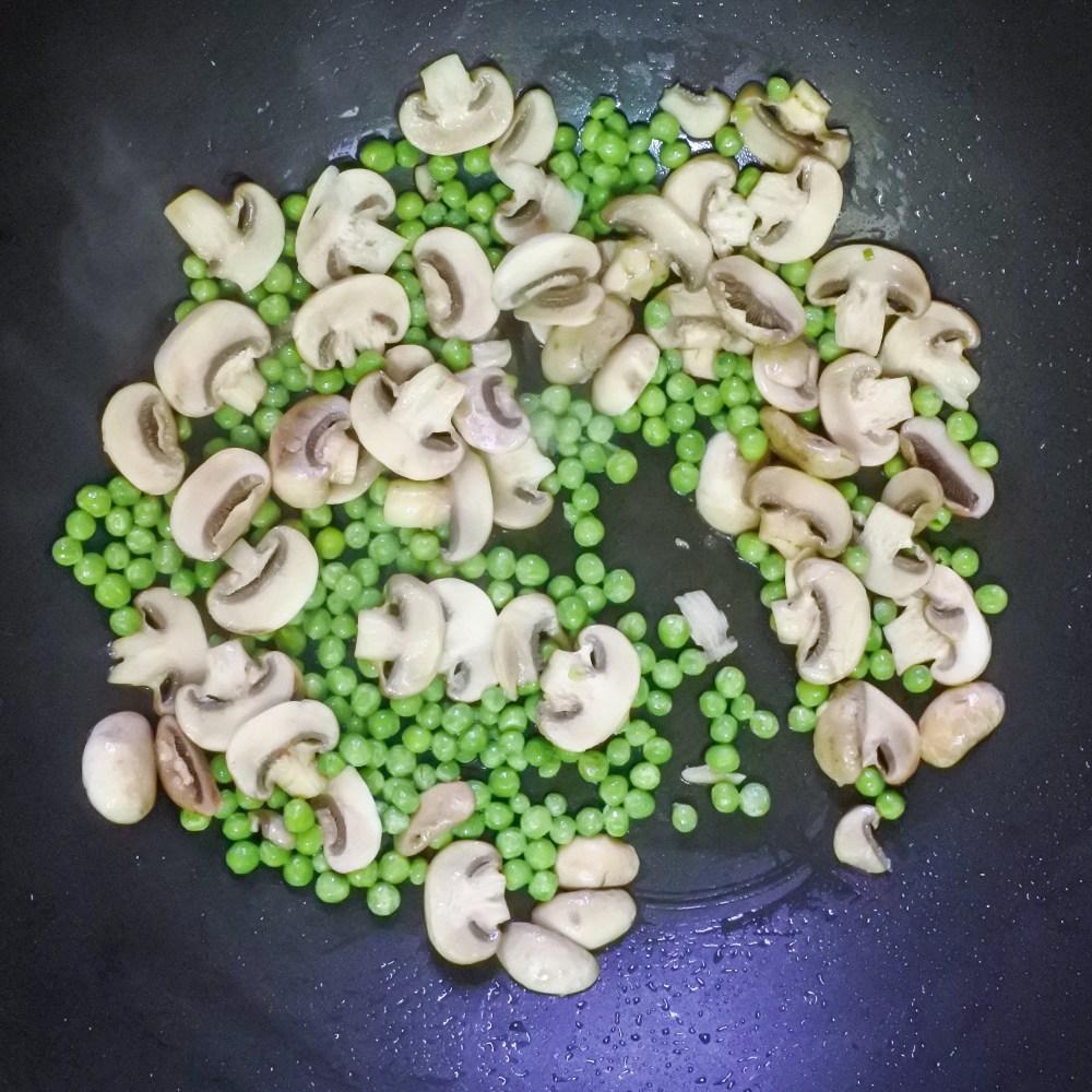 mushrooms and peas cooking in pan