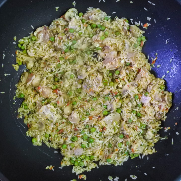 chicken frying with rice mixture in pan