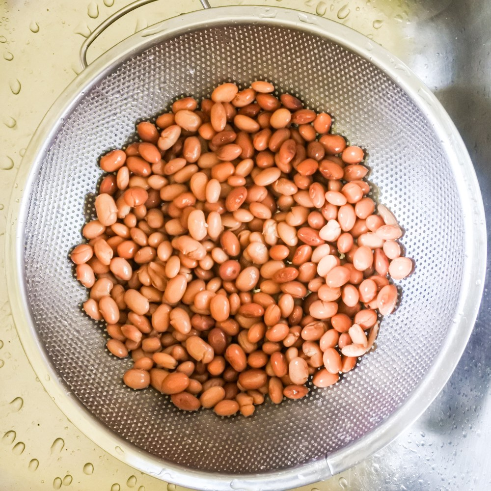 drained beans in a metal colander