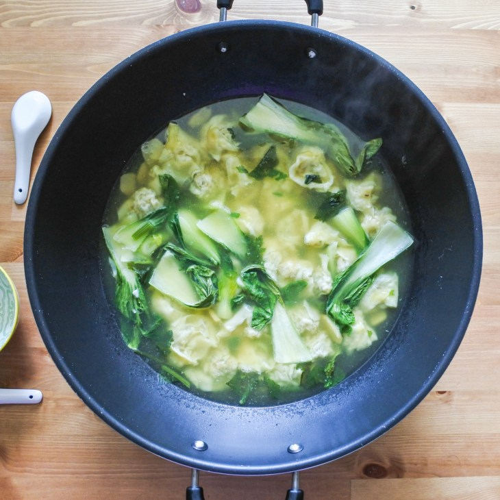 a large wok of wontons and bak choy in chicken broth