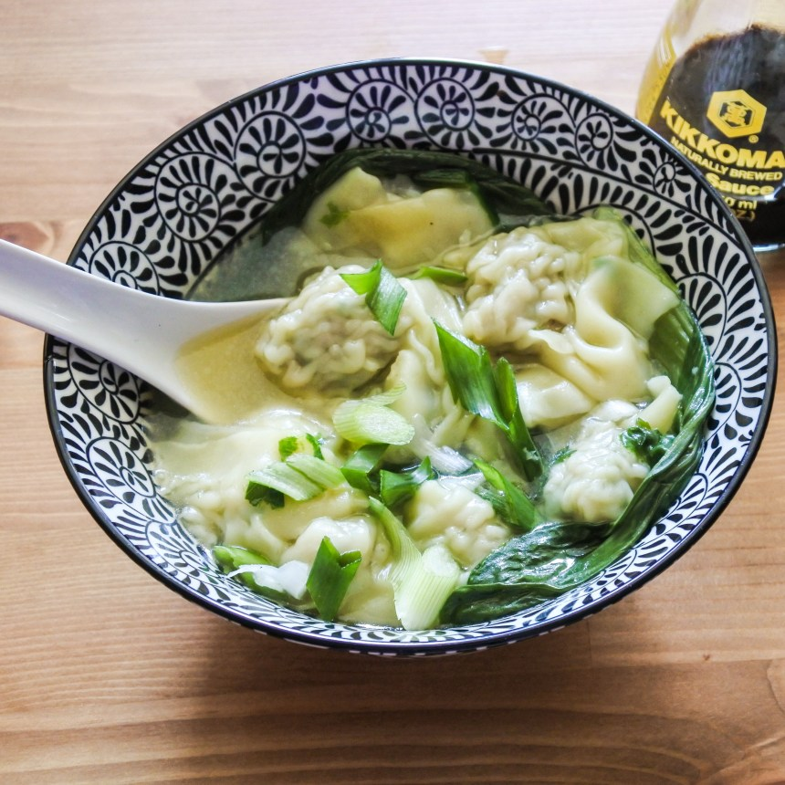 wontons and bak choy in chicken broth in a bowl with soy sauce