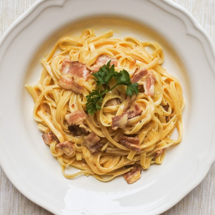 Pasta Carbonara garnished with a sprig of parsley