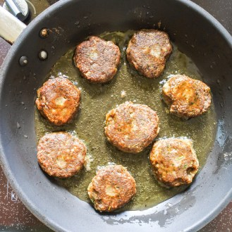 Lentil cakes frying in a pan