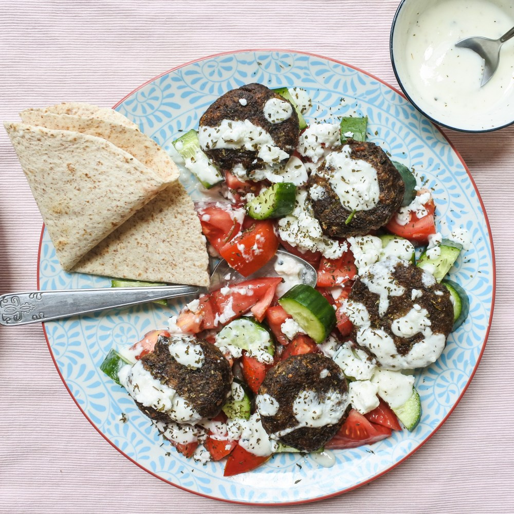 Lentil cakes over a salad of cucumber and tomato salad topped with a yogurt dressing and feta cheese served with a tortilla