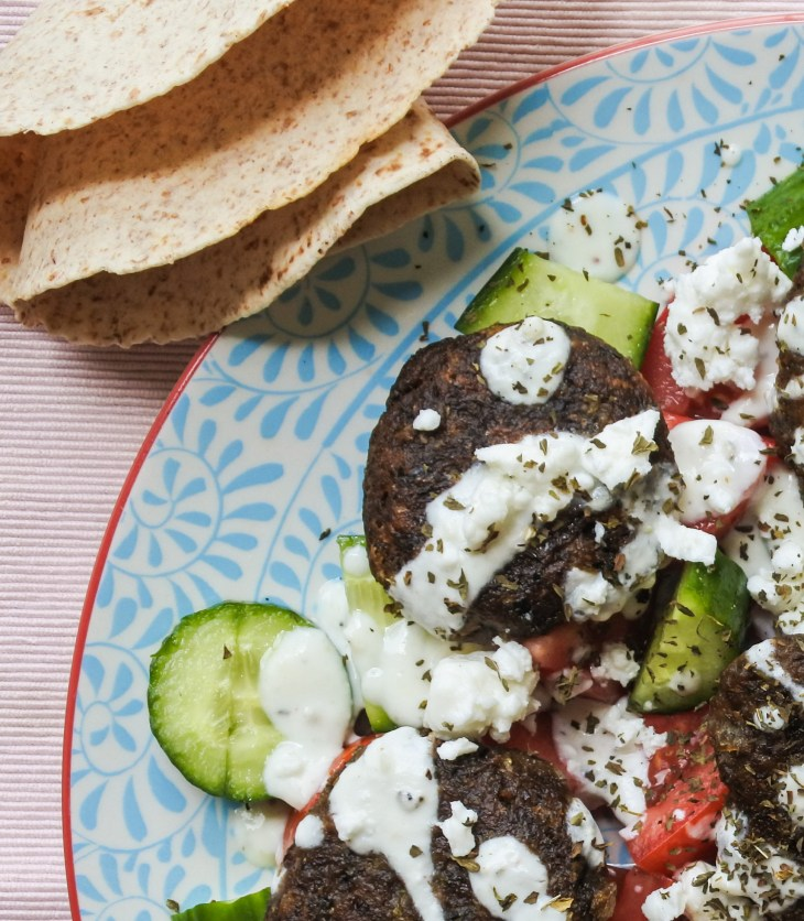 Lentil cakes over a tomato and cucumber salad with yogurt dressing and a tortilla