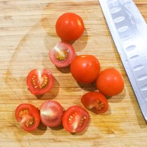 Wash and dry cherry tomatoes. Cut into halves.