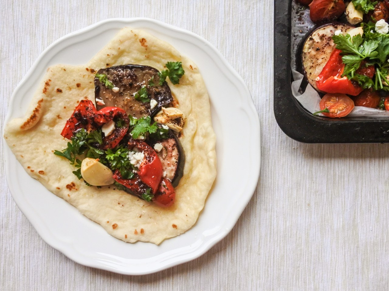 Sumac roasted vegetables garnished with feta and chopped parsley on naan bread
