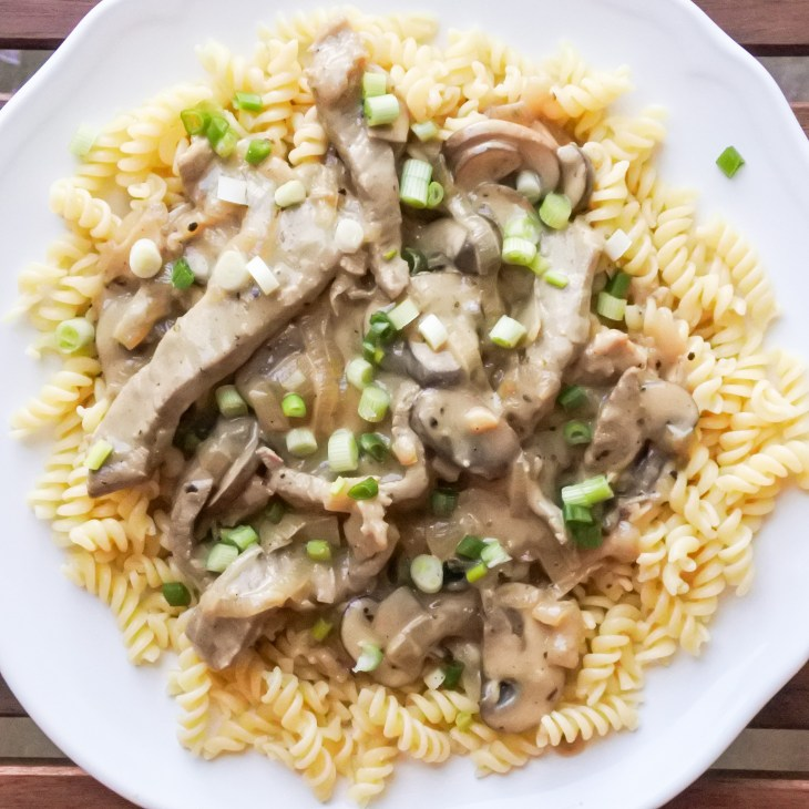 Beef and mushroom Stoganoff served atop corkscrew pasta and garnished with chopped scallions