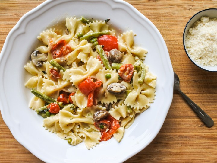Farfalle pasta tossed with roasted veg and cream served alongside grated Parmesan cheese