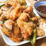 Salted fried chicken with scallions and onions served with Chinese chile oil