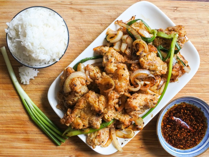 Salted fried chicken with scallions and onions served with a bowl of rice and Chinese chile oil
