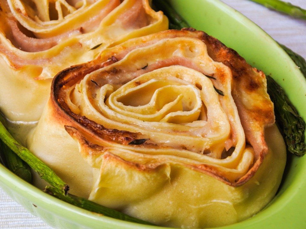 Rolled up pasta with ham and cheese served with asparagus in an oven dish