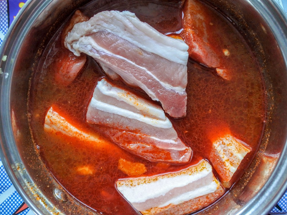 meat with ginger and garlic in chili broth in a pot