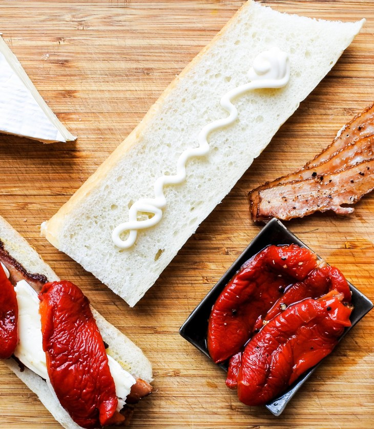 Brie cheese, sandwich, roasted red bell pepper and strips of bacon on a wooden cutting board