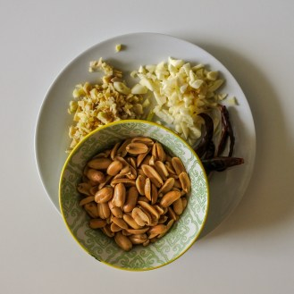 a bowl of peanuts with chopped ginger and garlic